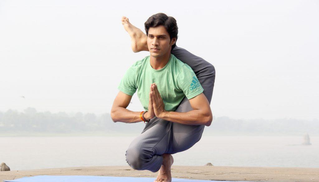 Ein Yogi in schwieriger Yoga-Haltung - auf den Zehenspitzen stehend, Hände in Gebetshaltung und den zweiten Fuß hinterm Kopf